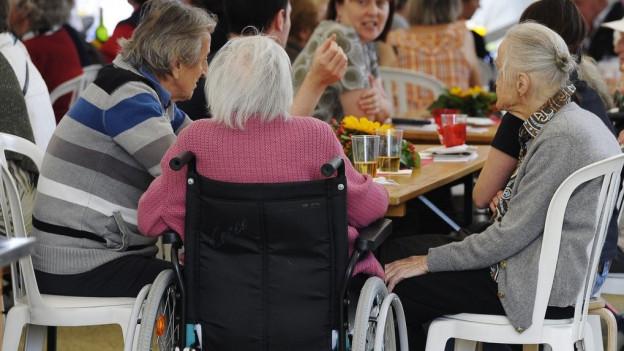 Eine Gruppe von Seniorinnen sitzen um einen Tisch.