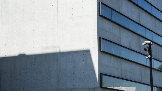 Ein modernes Betongebäude, davor eine Überwachungskamera