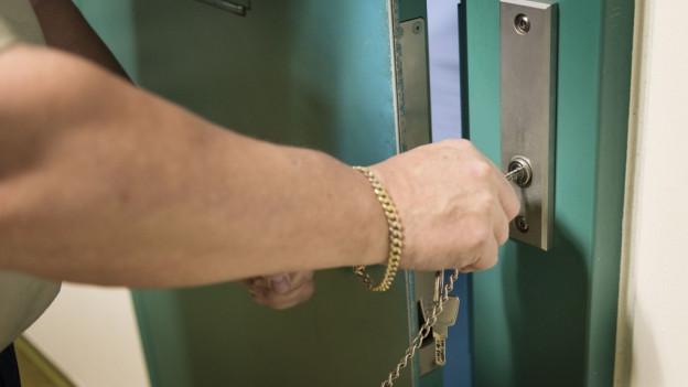 Eine Hand dreht einen Schlüssel in der Zellentüre in einem Gefängnis.