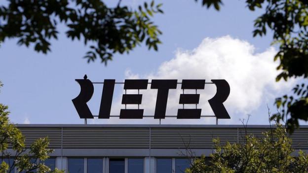 Rieter-Logo auf dem Dach der Fabrik in Winterthur, umrahmt von Laub