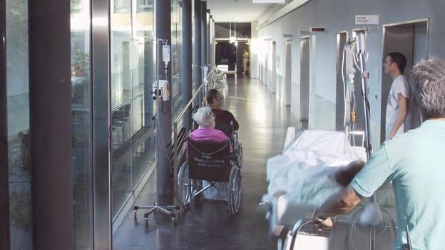 Blick in den Gang eines Spitals, eine ältere Frau im Rollstuhl.