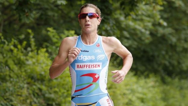 Eine Frau in hellblauem Läuferdress rennt