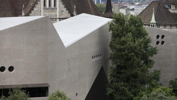 Eine moderne, gezackte Betonwand, dahinter ein schlossähnliches Gebäude.