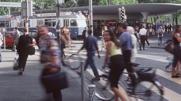 Viele Leute am Belleve, eine Frau schiebt ein Velo über einen Fussgängerstreifen.