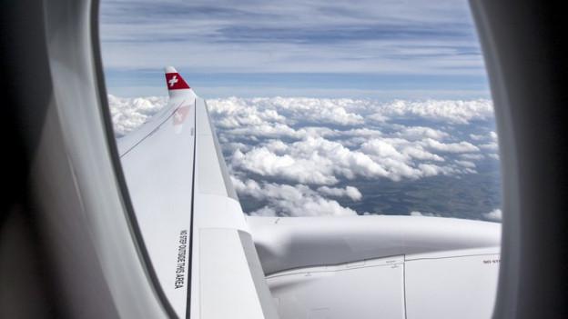 Blick aus dem Flugzeugfenster - Wolken, ein Flügel, am äussersten Rand ein Schweizerkreuz.