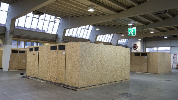 Kleine Häuschen aus Spanplatten in einer Halle.