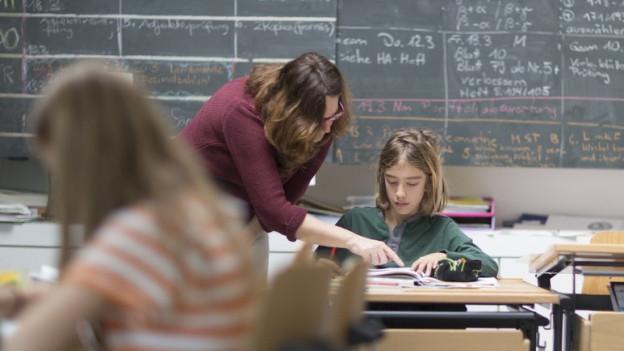 Eine Lehrerin beugt sich zu einem Schüler an einem Pult.