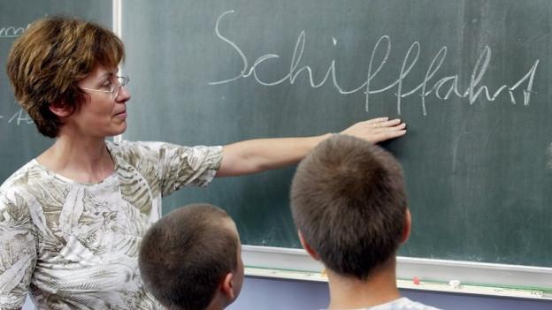 Eine Lehrerin erklärt die Rechtschreibung an der Wandtafel
