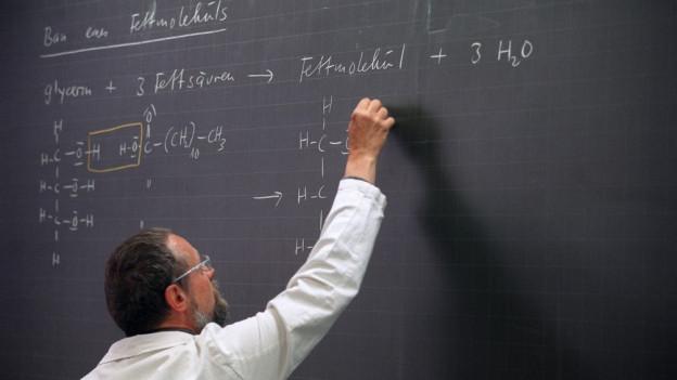 Ein Lehrer schreibt eine Chemieformel auf die Wandtafel.