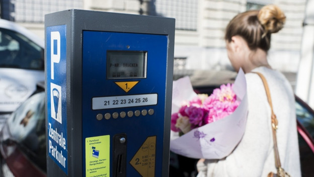 Eine Parkuhr in der Stadt, davor eine Frau mit Blumenstrauss