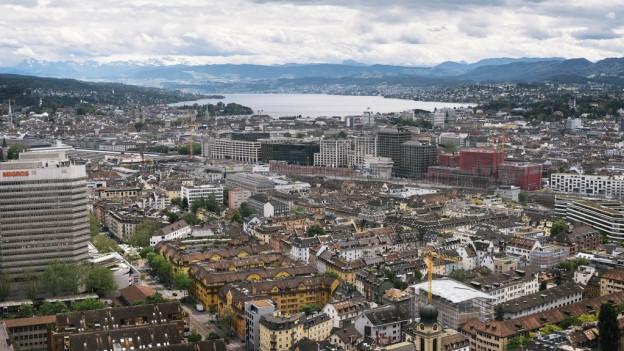 Blick von oben auf Stadt Zürich, im Hintergrund der See