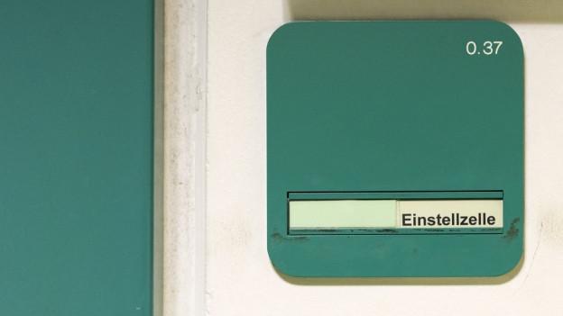 """Eine Tür, daneben ein grünes Schild, darauf steht """"Einstellzelle""""."""