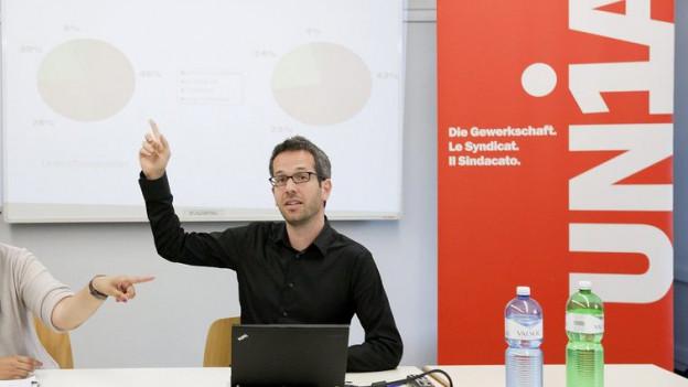 Ein junger Mann vor dem Computer hebt die Hand und spricht zum Publikum.