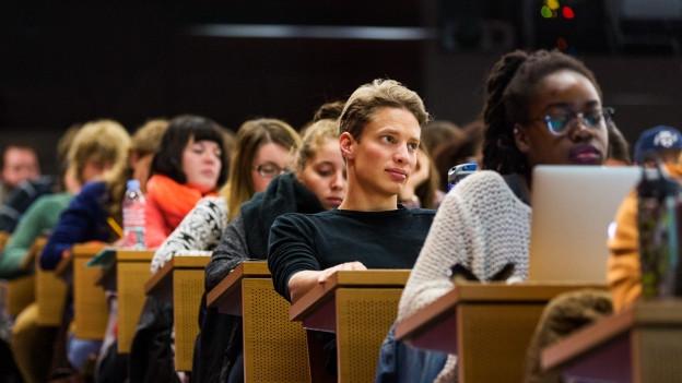Studentinnen und Studenten in einem Vorlesungssaal.