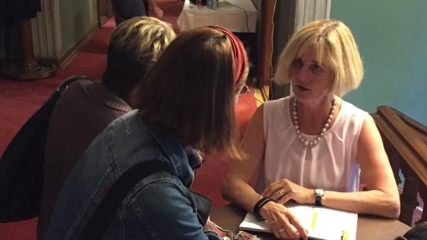 Regula Widmer an einem Stehtisch im Gespräch mit zwei Frauen.