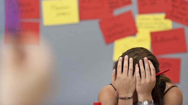 Ein Frau stützt den Kopf in die Hände, hinter ihr viele bunte Zettel.