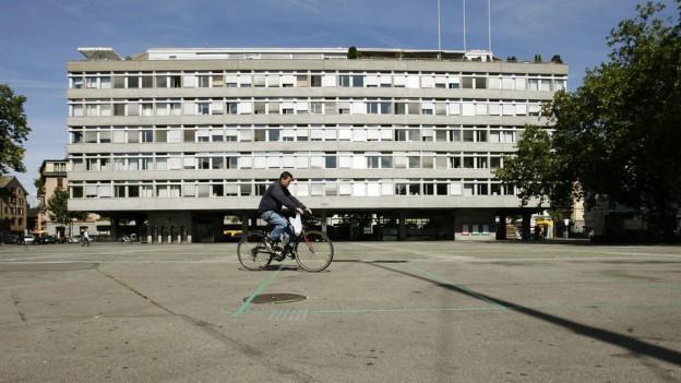 Ein Fahrradfahrer fährt über einen grossen Platz, dahinter ein Amtsgebäude auf Stelzen.