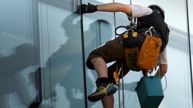 Ein Gebäudereiniger hängt angeseilt an deiner Glasfasade.