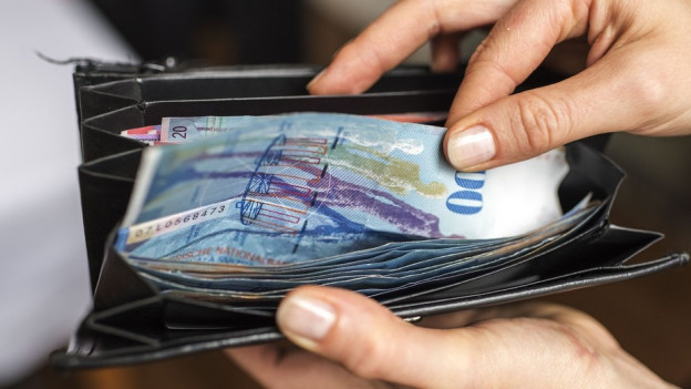 Eine Hand greift ins Portemonnaie und zückt einen Hunderter