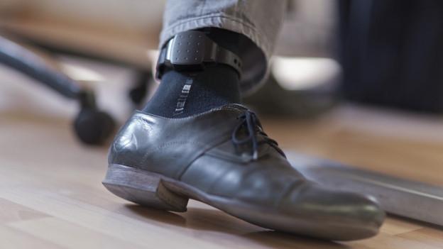 Fuss mit elegantem Männerschu und dem Sender über einer schwarzen Socke.