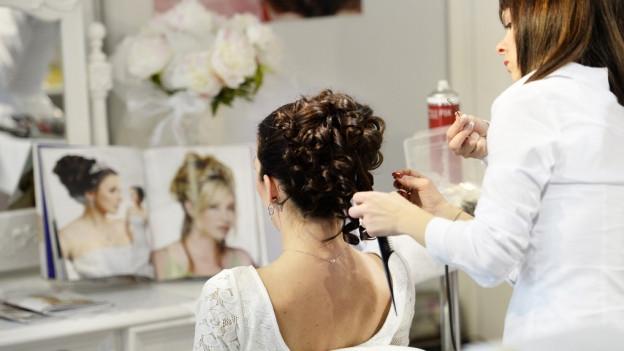 Eine Frau im Hochzeitskleid wird frisiert
