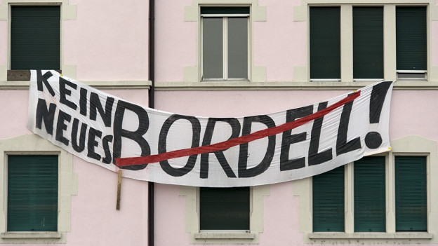 """Zwischen zwei Fenstern hängt ein Banner mit der Aufschrift """"Kein neues Bordell"""""""