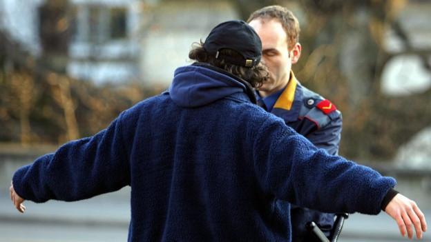 Mann mit ausgebreiteten Armen und Polizist