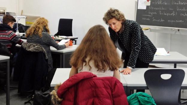 Eine Lehrerin hilft einer Schülerin beim Lösen der Aufgaben.