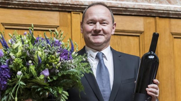 Mann mit Krawatte und Anzug und Blumenstrauss strahlt