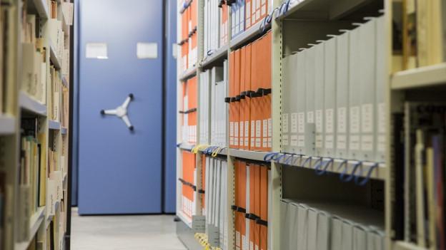 Ein langer Gang führt in Mitten zahlreicher Regale mit Büchern zu einem verschlossenen Aktenschrank.