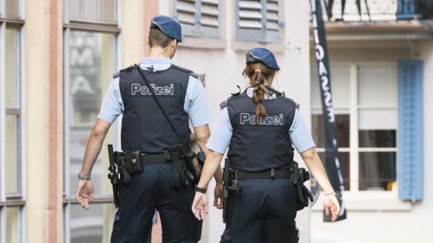 Zwei Polizisten laufen durch Strasse.