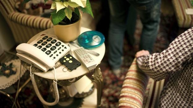 Frau in altem Sessen neben Telefon