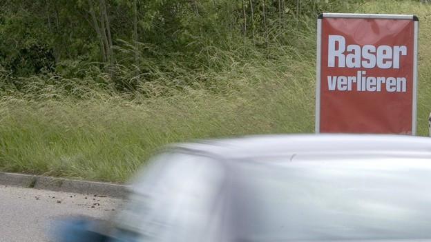 """Ein Auto fährt schnell an einem Schild vorbei, darauf steht """"Raser verlieren"""""""