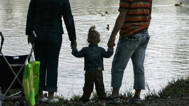 Eine Frau und ein Mann halten ein kleines Mädchen an den Händen.