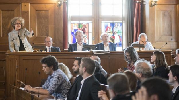 Blick ins Zürcher Stadtparlament. Männer und Frauen sitzen in Bänken, dahinter eine Frau, die auf die Leute zeigt.