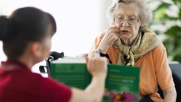 Eine Pflegerin liest einer Seniorin ein Buch vor.