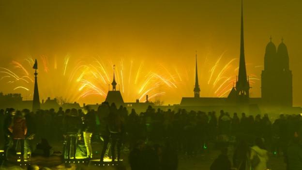 Menschen betrachten von der Polyterasse aus den Feuerzauber am Himmel