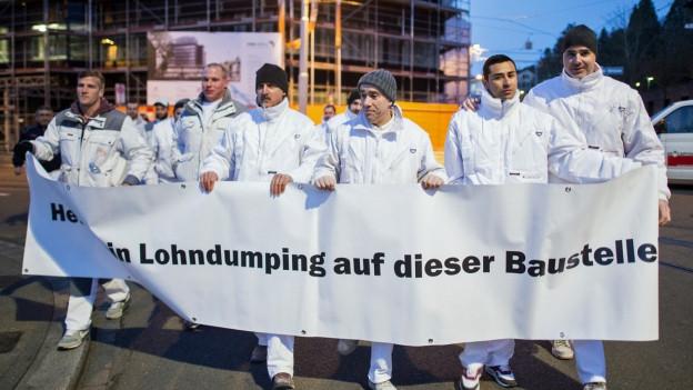 Weiss gekleidete Bauarbeiter demonstrieren gegen Lohndumping und halten ein Transparent mit einer entsprechenden Aufschrift in die Höhe.