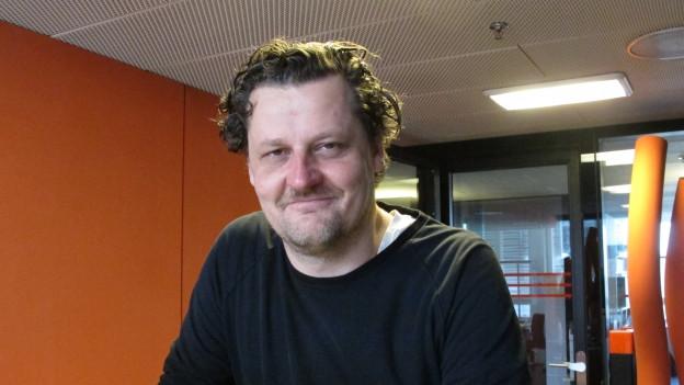 Ein Mann mit markantem Gesicht im Radiostudio.