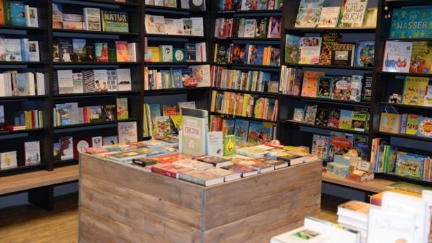 Eine Buchhandlung mit schwarzen Gestellen, darin farbige Bücher, in der Mitte ein heller Holztisch.