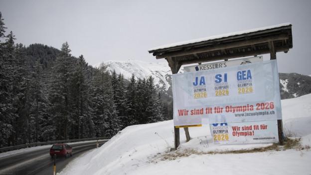 Plakat für Olympia auf einer Bündner Wiese.