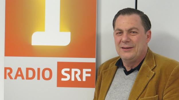 Ein Mann steht vor dem Radio SRF1-Logo