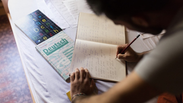 Ein Migrant sitzt vor einem Lehrbuch und übt die deutsche Sprache.