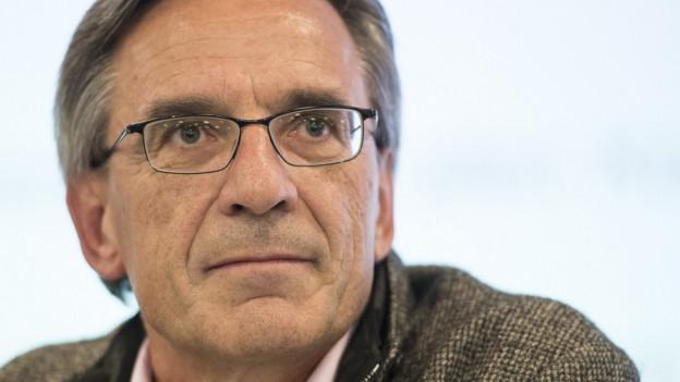 Hans-Ulrich Lehmann, älterer Mann mit Brille schaut an der Kamera vorbei.