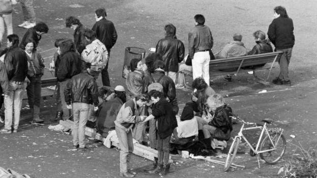 Szene auf dem Platzspitz, verschiene Menschengruppen, auf dem Boden Abfall.