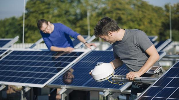 Männner arbeiten an blauen Solaranlagen.