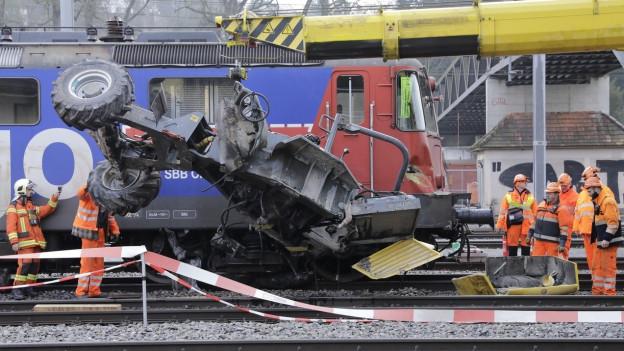 gelber Kran, zerstörtes Fahrzeug, orange gekleidete Bahnarbeiter