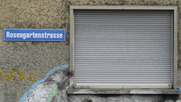"""dreckige Hausfassade, Fenster mit geschlossenen Rolläden, Strassenschild """"Rosengartenstrasse"""""""