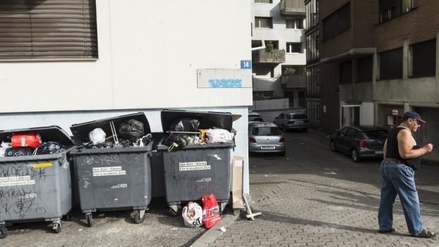 Drei Container voller Abfall vor einer Hauswand