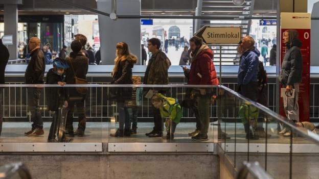 Mehrere Leute stehen Schlange vor dem Stimmlokal im Zürcher Hauptbahnhof.